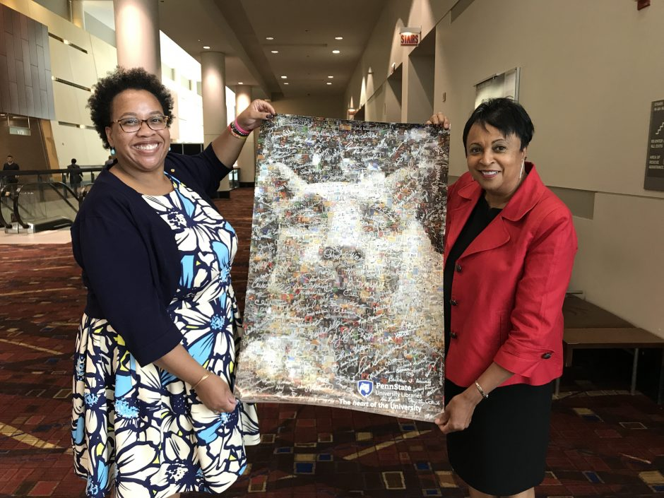 two African-American professional women holding vertical poster composed of hundreds of digitzed images from Penn State University Libraires' special collections, forming a composite image of Penn State's Nittany Lion Shrine stone sculpture. Poster is signed in silver ink by many Penn State Libraries employees.