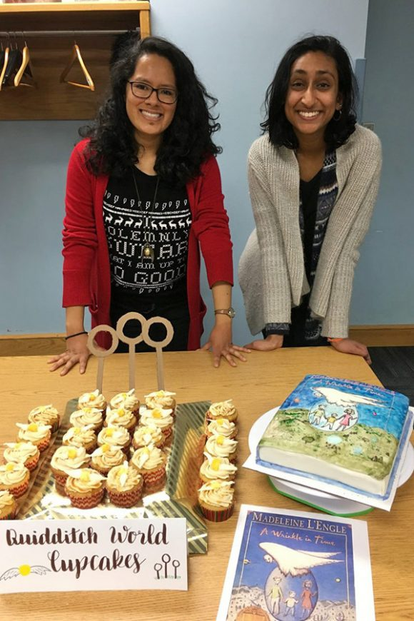 two women standing behind beautiful baked goods