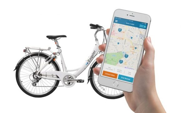 photo of bicycle next to a hand holding a smartphone showing the Zagster app