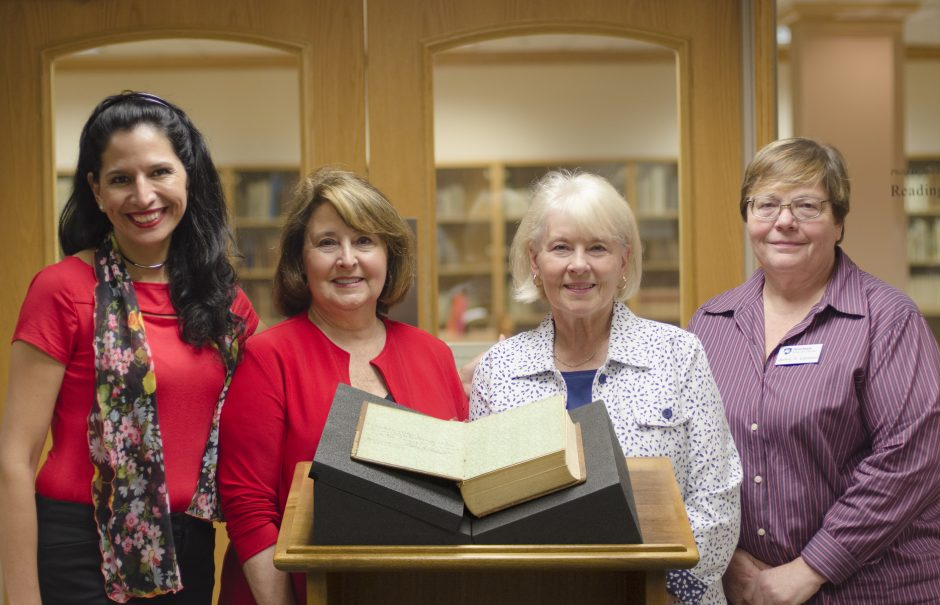 horizontal photo of four women standing behind rare book displayed on podium