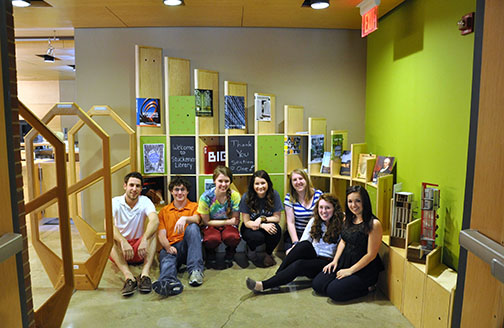 students seated in front of shelves