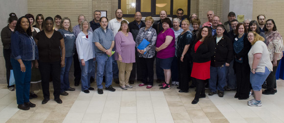 horizontal group photo portrait of 34 people standing in Pattee Library's Franklin Atrium