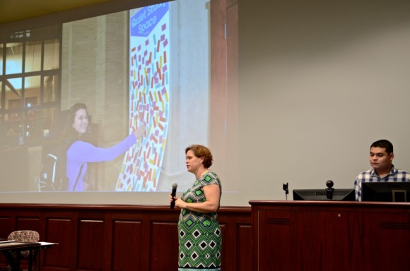 woman standing in front of large wall with projection of images; man sitting at right behind podium