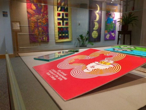 horizontal photo of glass exhibit case showing a red Arts Festival program from the 1970s, with festival banners hanging in the background