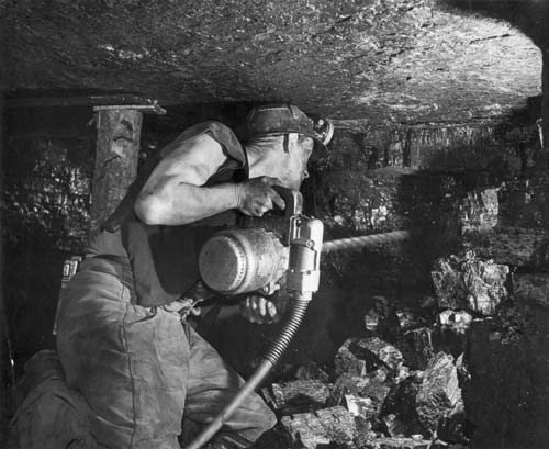 A miner drilling into the seam. This photograph shows how hard the work is for a face worker. The heavy drill, the noise, dust, lack of headroom, kneeling on rough ground and the constant danger.