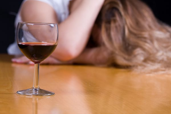 a glass of wine in front of a despondent-looking woman in the background