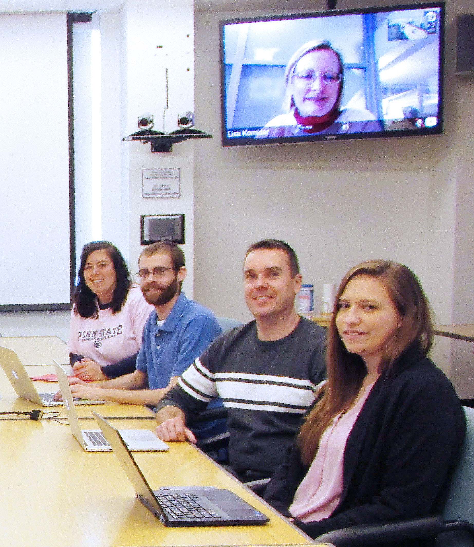 Photo of members of the Outreach conversion team, including Dawn Coder, John Butler, Linas Mockus and Ashlyn Brickley seated at a table, with Lisa Komidar on the screen behind them.
