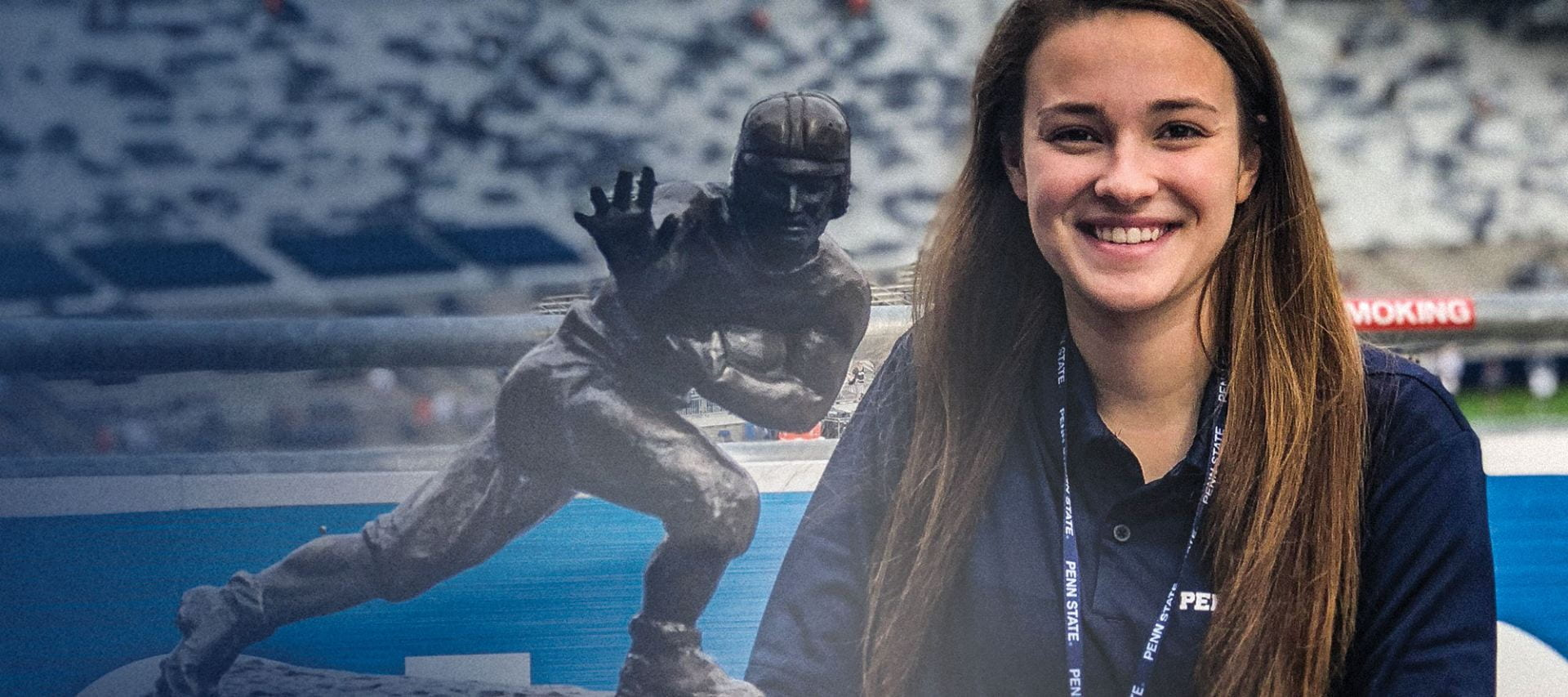 Penn Stater, Taylor Machuga standing with the Heisman Trophy at Beaver Stadium.