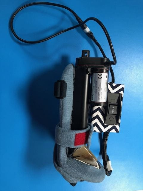 Photo of the Mano ROM device, a gray cloth sleeve with the mechanical components of the device and wires attached