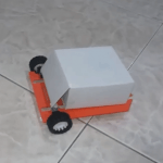 Photo of small cube shaped robot with orange base on wheels