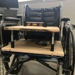 Photo of a prototype of the product, a wooden seat with four pistons that is resting on top of a wheelchair seat