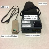 ToeTronics has a main module that allows a foot to be placed on top of it. It contains a foot strap, two attachments for a forefoot strap, toe strap, force plate, and on-device display. Connected to the front of the main module is a data logging module with a USB cord.