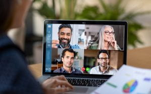 Back view of business woman talking to her colleagues about business plan in video conference. Multiethnic business team using laptop for a online meeting in video call. Group of buinessmen and businesswomen smart working from home.