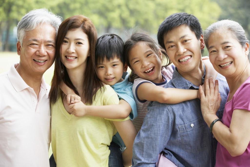 Portrait Of Multi-Generation Chinese Family Relaxing In Park Tog