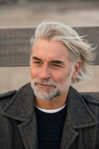 Mature man with long grey hair smiling