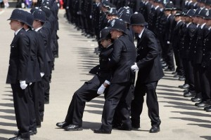 a-police-officer-is-caught-by-colleagues-as-he-becomes-faint-during-a-passing-out-parade