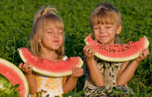Little blond girl and boy with a piece of watermelon in hands