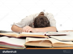 stock-photo-tired-teenager-lying-and-sleeping-on-the-school-desk-121132150