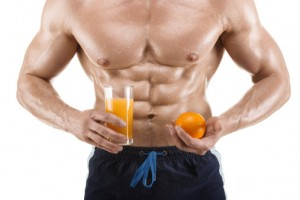 healthy muscular man holding a glass with juice and orange