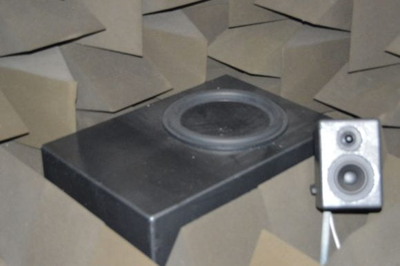 Sub-woofer positioned in the rear-right corner of the chamber
