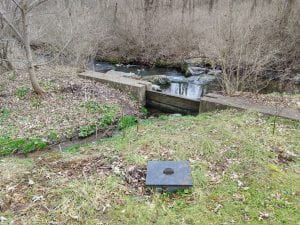 Concrete weir and pipe inflow points to constructed wetland
