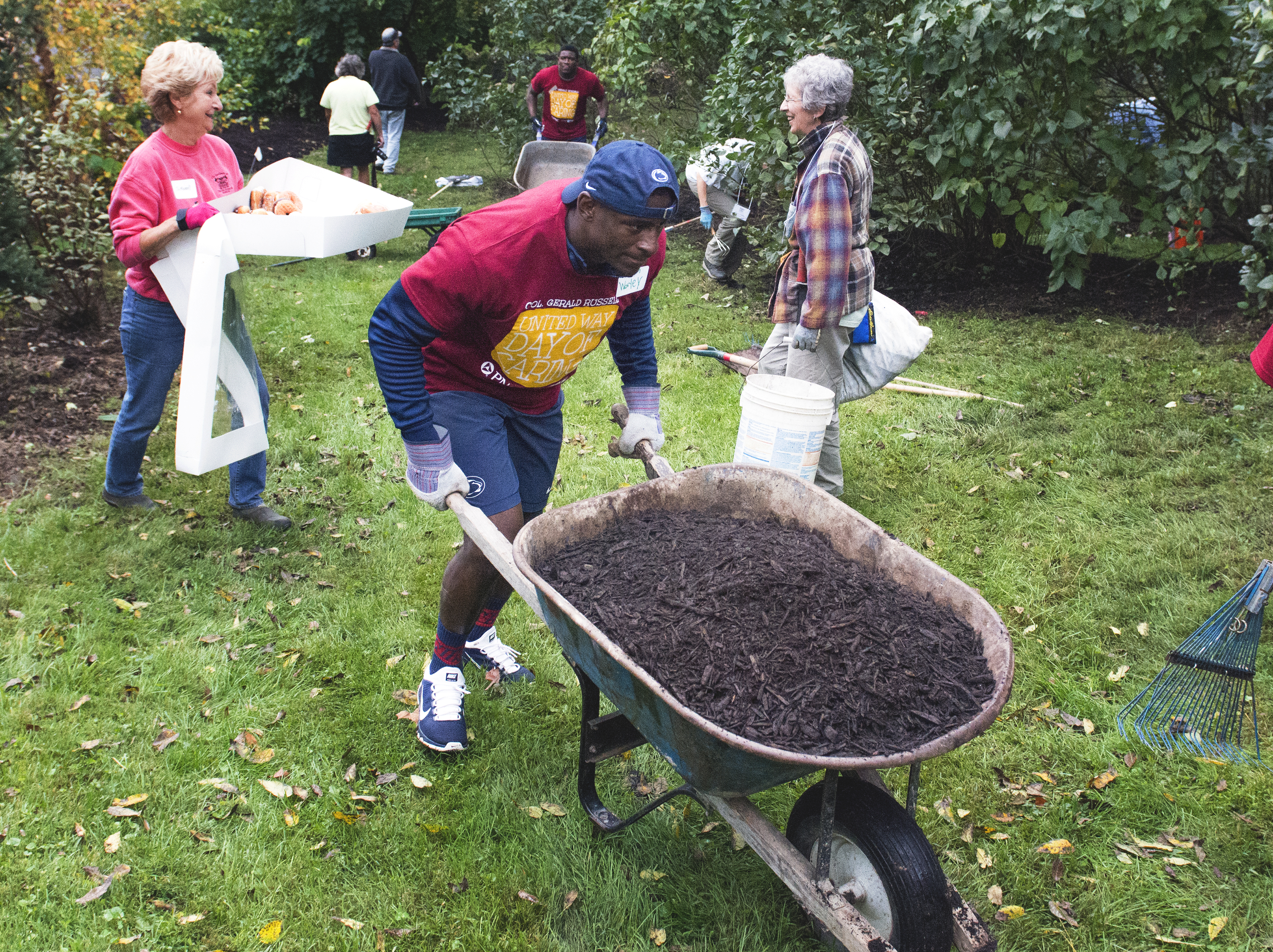 Penn State football player pushes wheelbarrow at PNC Day of Caring